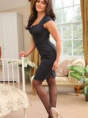 """Busty bubbly Kat in black stockings and suspenders"""